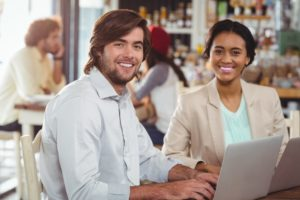Man and woman using laptop during meeting in cafe technology flexible working